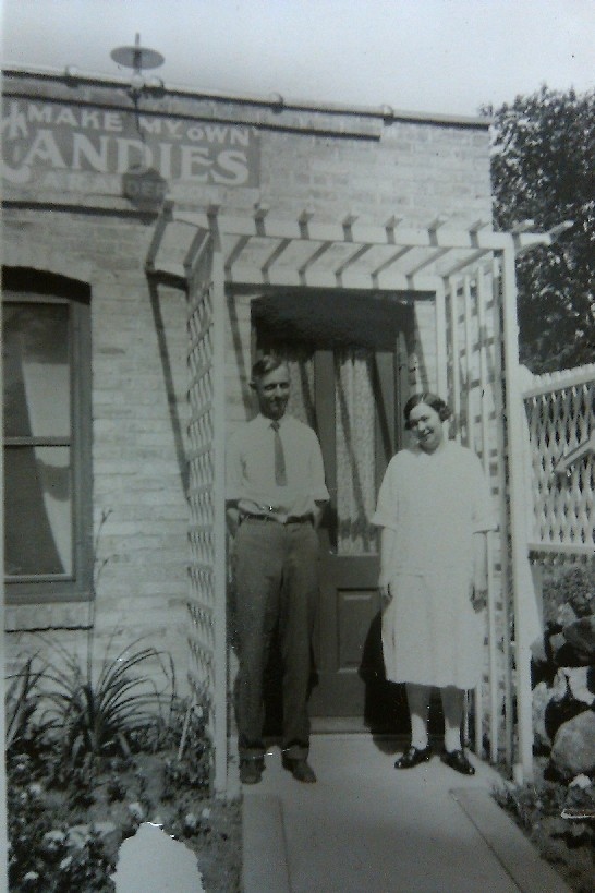 Arthur and Gertrude (the founders of Anderson's Candy Shop) stand outside of their business. The sign above their heads reads: I MAKE MY OWN CANDIES
